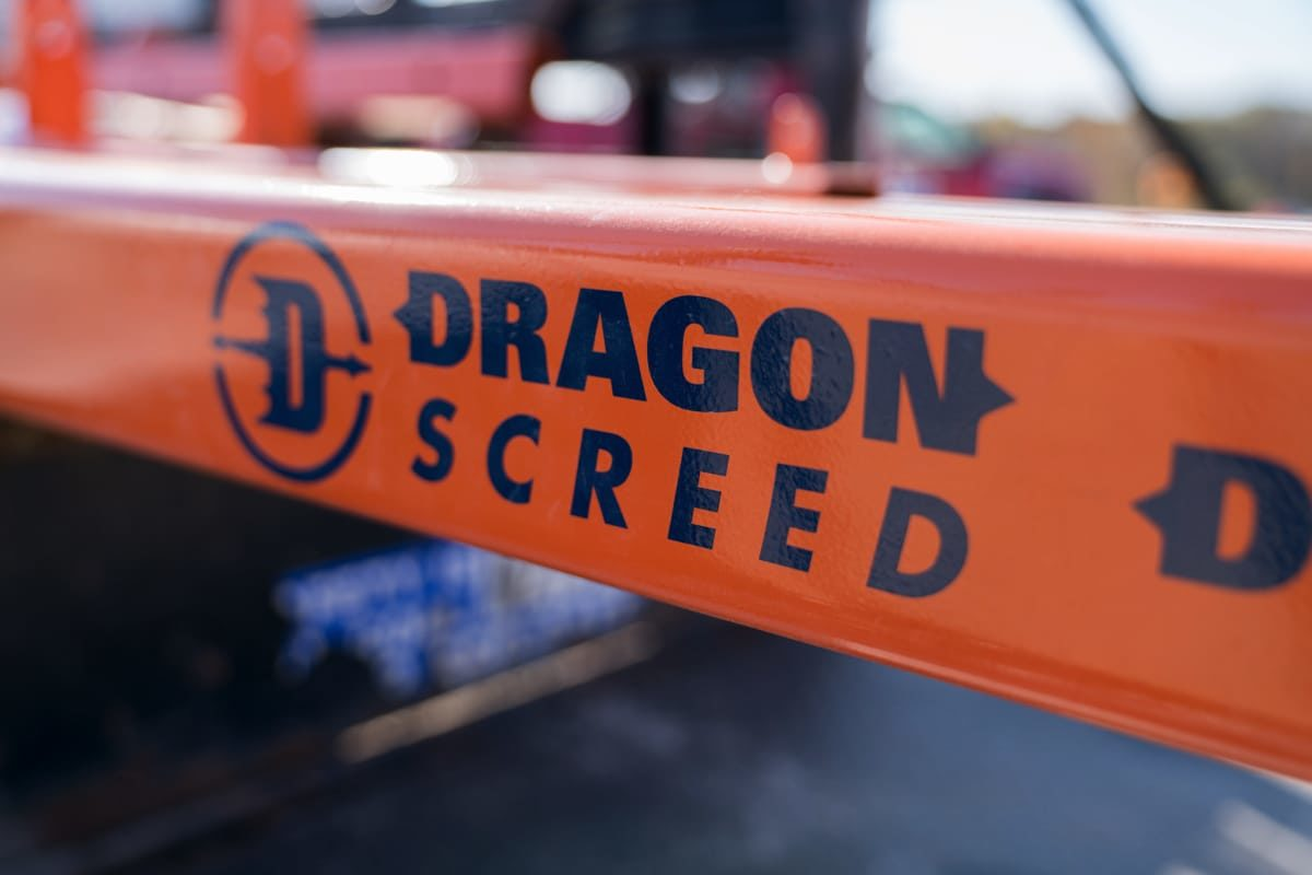 "Dragon Screed logo on orange skid steer attachment - features a flying dragon with the body in the shape of a ""D""."