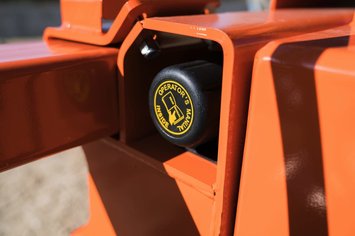 Dragon Screed user manual stored inside a permanent tube fixture attached to the main body of the skid steer attachment housing.