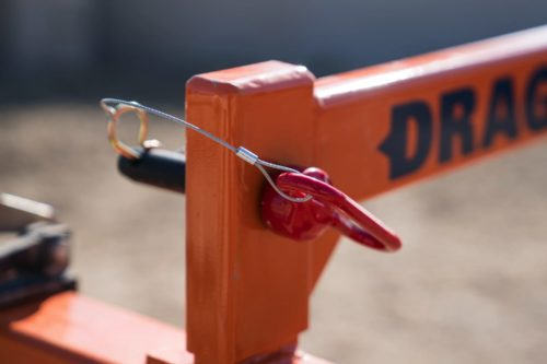 Pin that holds two pieces of orange steel together on the Dragon Screed. These pins allow the user to switch back and forth between a vibrating concrete screed and gravel grader.