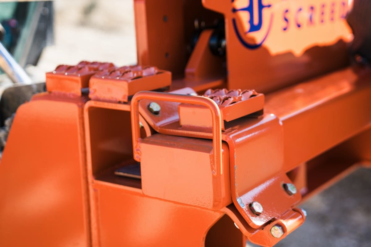 Orange step on the screed's main housing unit, where users place their foot when climbing into and out of a bobcat or skid steer.