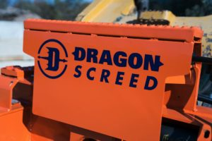 Front of a Dragon Screed skid steer attachment, with dragon logo on signature orange paint.
