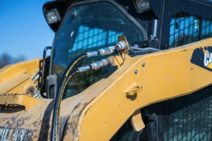 Dragon Screed's hydraulic hoses plugged into the front of a CAT skid steer.