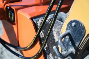 Close up of hydraulic hoses that plug the concrete screed into the skid steer.