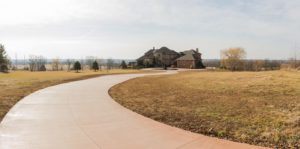 A long, winding driveway leads a beautiful home on a hill. This concrete driveway was poured using a Dragon Screed - a vibrating concrete screed that attaches to a bobcat machine.
