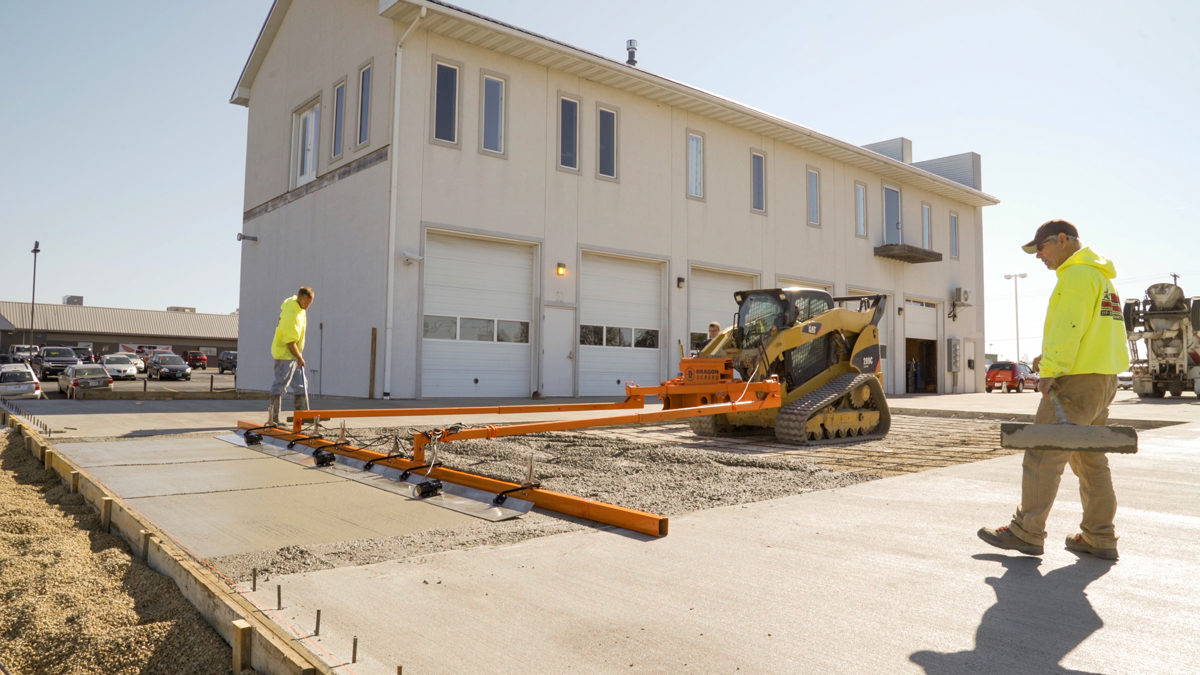 Two construction laborers watch as a powered concrete screed levels wet concrete on a new parking lot.