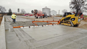 A concrete laborer stands in wet concrete watching a screed machine level concrete. Dragon Screed is a powered concrete screed that attaches to the front of a machine.