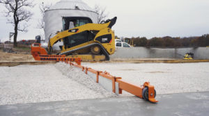 A machine-powered concrete screed grades gravel on a construction site.