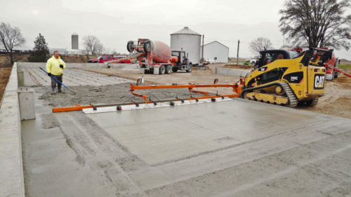 A concrete laborer stands in wet concrete watching a skid steer level concrete with Dragon Screed. Dragon screed is a bobcat attachment that attaches to the front of a machine. It has an screed arm that reaches off to the side of them machine and levels and vibrates concrete.