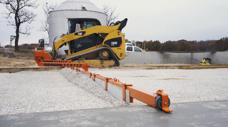 Dragon Screed grades gravel base on a concrete floor. This skid steer powered concrete screed machine can be configured as gravel grader or concrete screed.