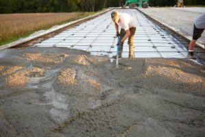 A concrete laborer rakes concrete using a come-along. Come-alongs are used on flatwork projects to level the concrete prior to screeding.