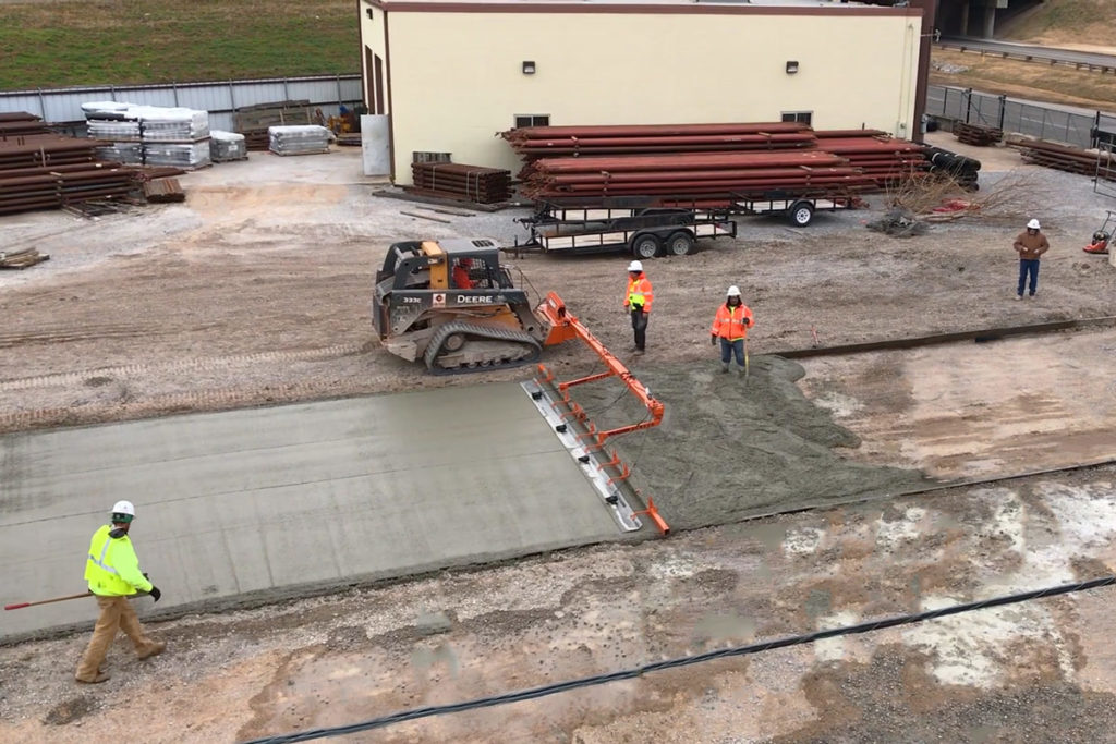 Dragons Screed, a skid steer powered concrete screed machine, screeds a concrete driveway using a hydraulic pivot and vibrating screed bar and floats.