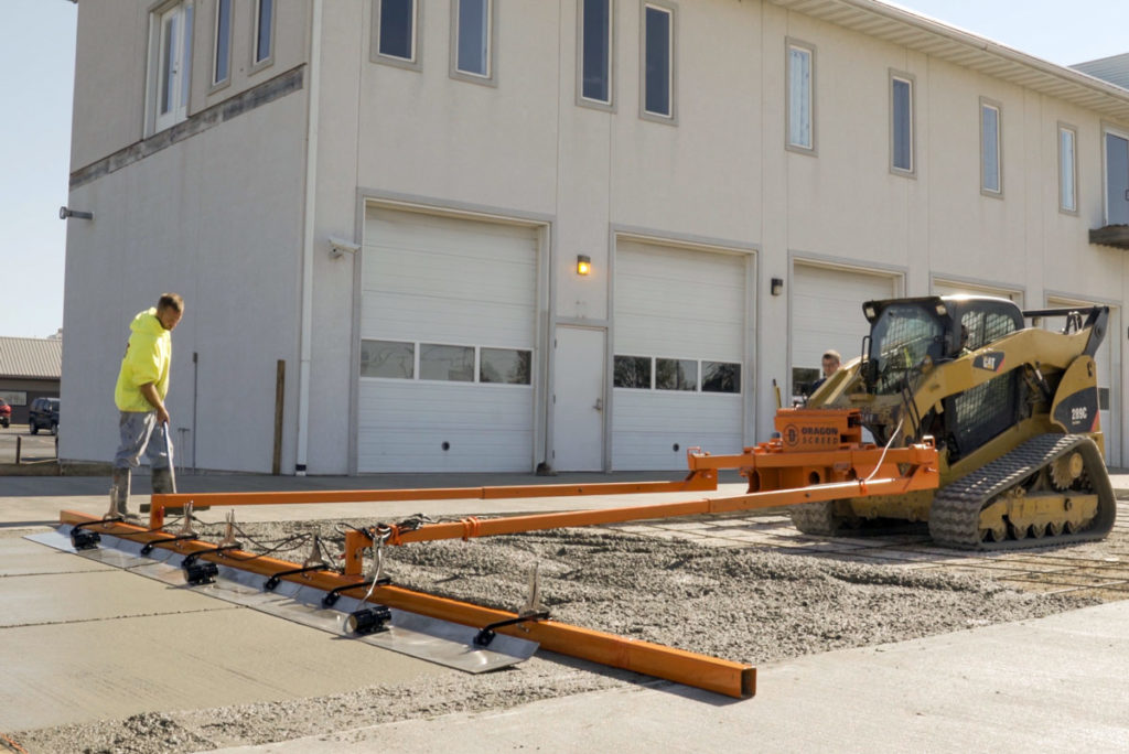 A concrete screed, attached to the front of a skid steer machine, levels concrete on a construction site.