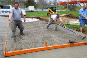A concrete crew pulls a small vibrating screed over a freshly poured truckload of concrete.