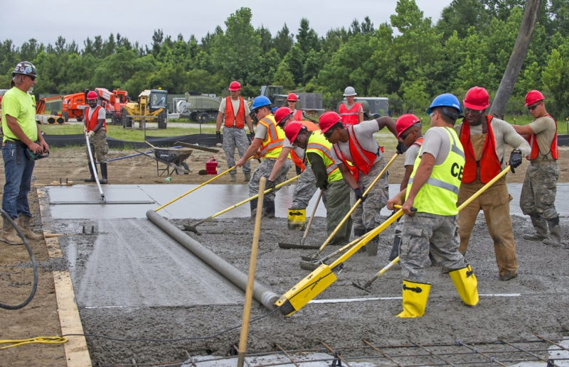 A construction crew pours concrete using a roller screed. Roller screeds level concrete reasonably well, but require a lot physical labor and effort in both pulling the screed and raking the concrete.