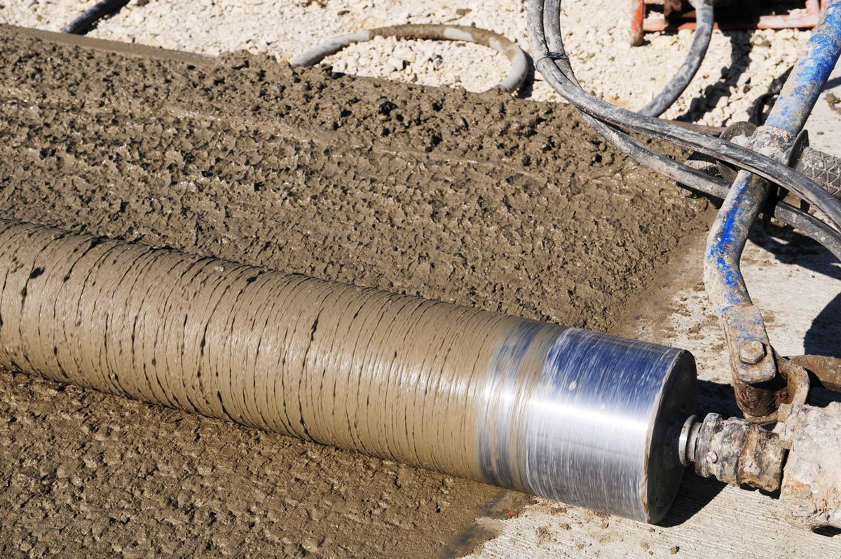 A roller screed is used to level concrete on a freshly poured driveway. Roller screeds are arguably the best concrete screed type for use on extremely small pours like patios or short sidewalks..