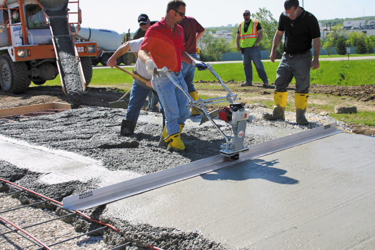 A concrete contractor screeds freshly poured concrete with a vibra strike screed. Stand-up screeds are gas-powered and vibratory. The user typically stands in the concrete and pulls the screed along a screed pipe.