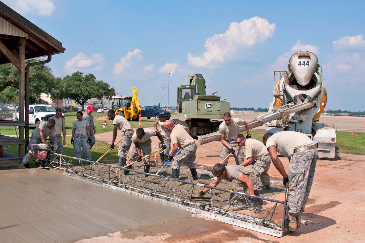 A crew pours a slab of concrete using a truss screed, also known as an A-frame screed. Truss screeds are gas-powered and vibrate concrete aggregate down on flat concrete projects like driveways, parking lots and floors.