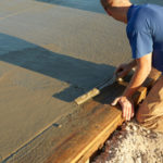 A concrete finisher uses a float to level and smooth out wet concrete.
