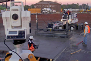 A laser-guided concrete screed levels concrete on a large parking lot. Laser-guided screeds are often the best concrete screed type when ultra high flatness ratings are required.