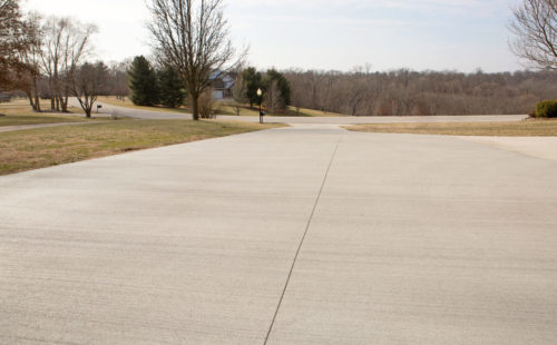 A flat concrete driveway with a broom finish and saw cuts is a great example of just how flat concrete can be poured when the proper tools and techniques are used.