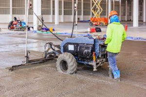 A contractor uses a laser screed to level wet concrete. Laser screeds tend be expensive, but the are the best concrete screed type when flatness is paramount.