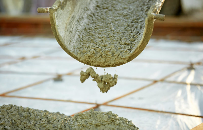 Wet concrete is poured from down a chute from a concrete truck. The concrete has a low slump rating - meaning that has a relatively low water content.