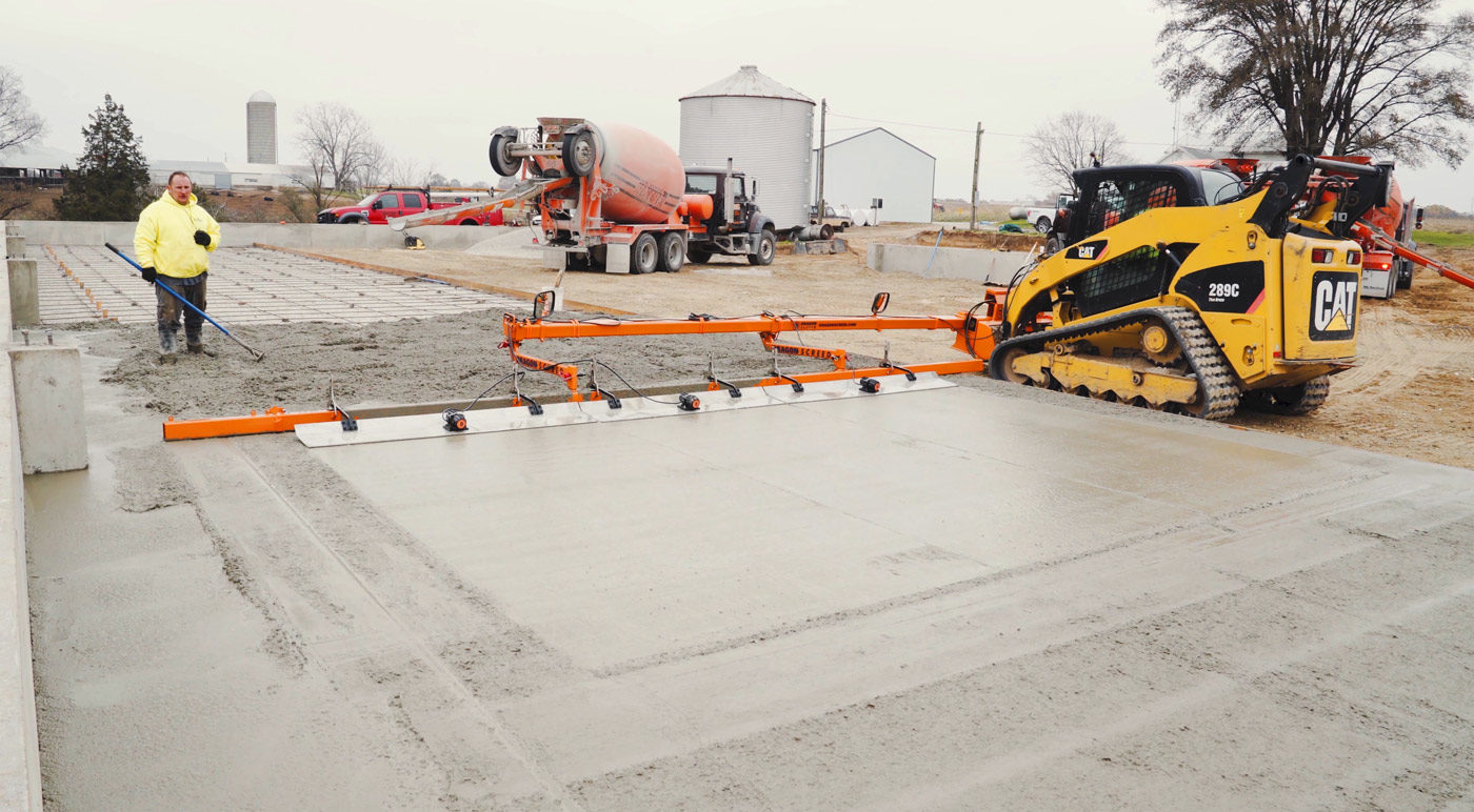 A screed, attached to a skid steer, levels freshly poured concrete. The machine is powered by the skid steer and includes a vibrating screed bar and vibrating floats.