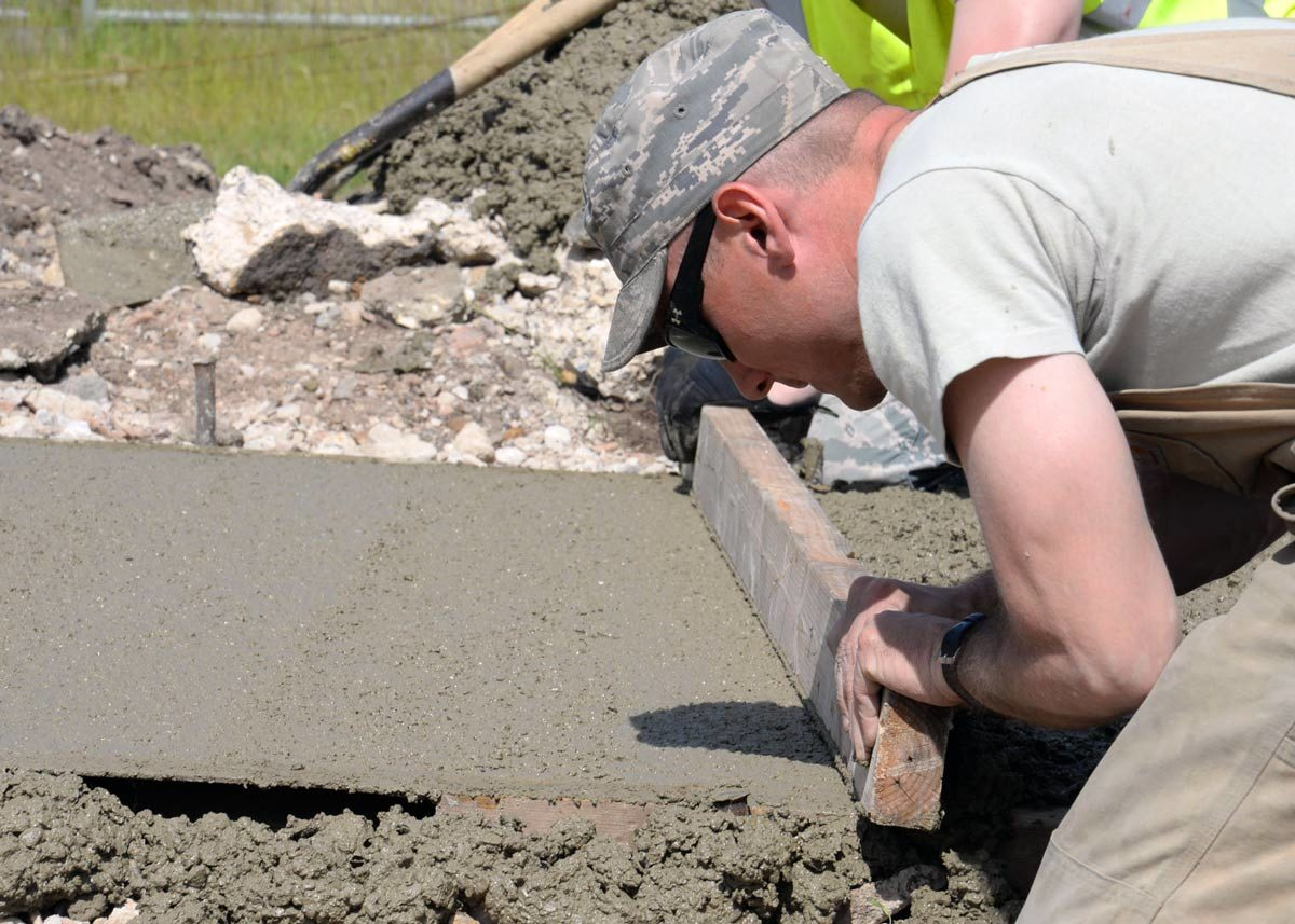 A concrete finisher uses a screed board to level wet concrete between the forms on a freshly poured sidewalk.