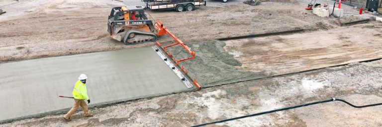 A machine-powered concrete screed levels a concrete driveway using a vibrating screed bar and floats.