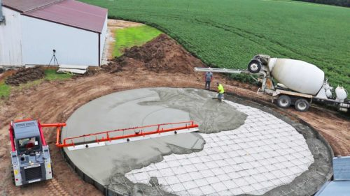 A contractor uses a screed model, made by Dragon Screed, that levels concrete on round pads and grain bins.