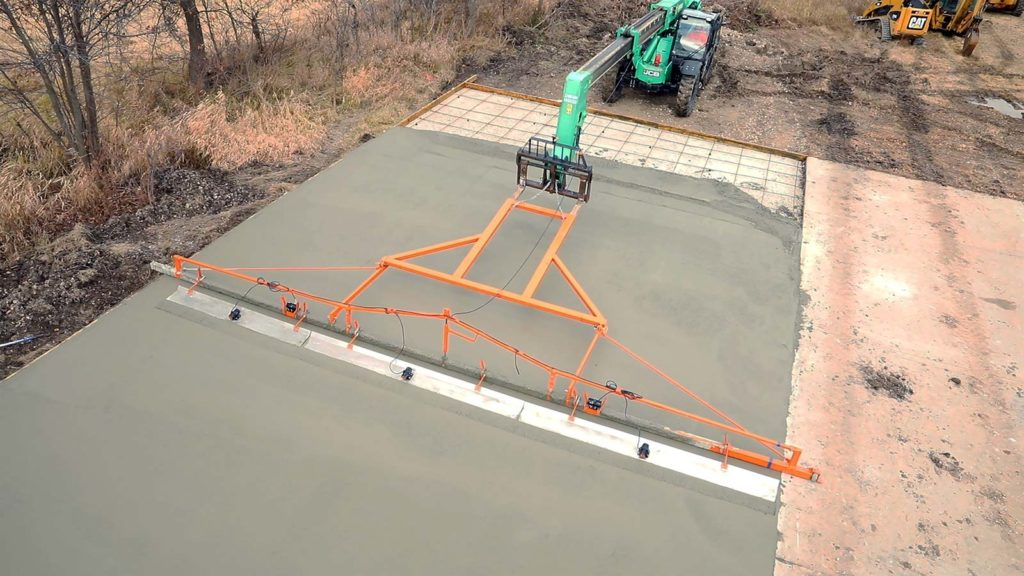 A telehander-powered concrete screed reaches out over freshly poured concrete to level and smooth out the slab.