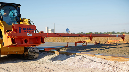 A Bobcat with a concrete screed attachment is used to level concrete on a construction site.