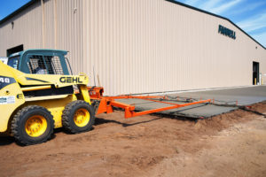 A concrete contractor uses a skid loader with a screed attachment to level freshly poured concrete.