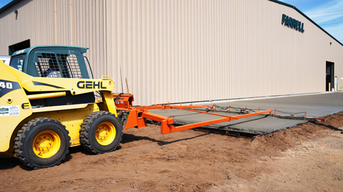 A concrete contractor levels freshly poured concrete using a skid loader with a screed attachment.