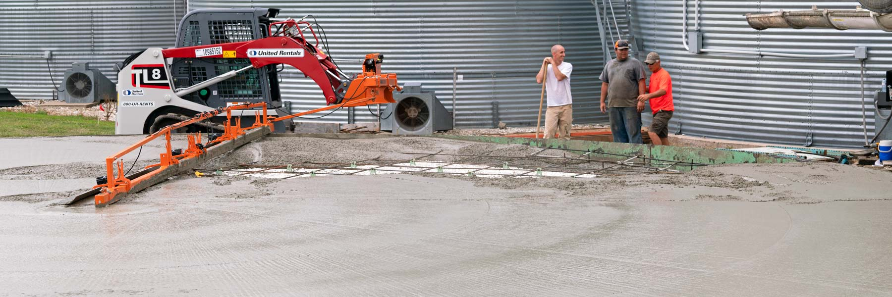 A happy concrete crew talks near a freshly poured concrete pad.