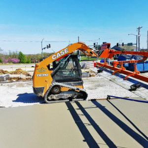 A skid steer sits parked on a construction site.