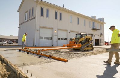 Two construction laborers watch as Dagon Screed (a skid steer powered concrete screed machine) screeds concrete on a newly poured parking lot. Dragon Screed is the ultimate concrete screed for pouring parking lots, driveways and floors.