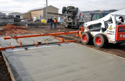 A skid steer, set up with a concrete screeding attachment, levels a newly poured concrete drive.